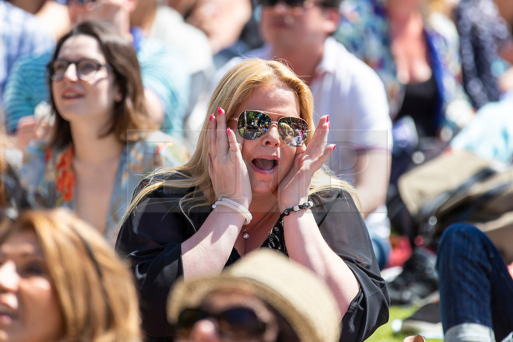 © Licensed to London News Pictures. 19/05/2018. London, UK. A woman wipes tears from beneath her sunglasses as well-wishers watch the Royal Wedding at an outdoor screening at the National Maritime Museum in Greenwich. Prince Harry is getting married to Meghan Markle today in Windsor. Photo credit: Rob Pinney/LNP