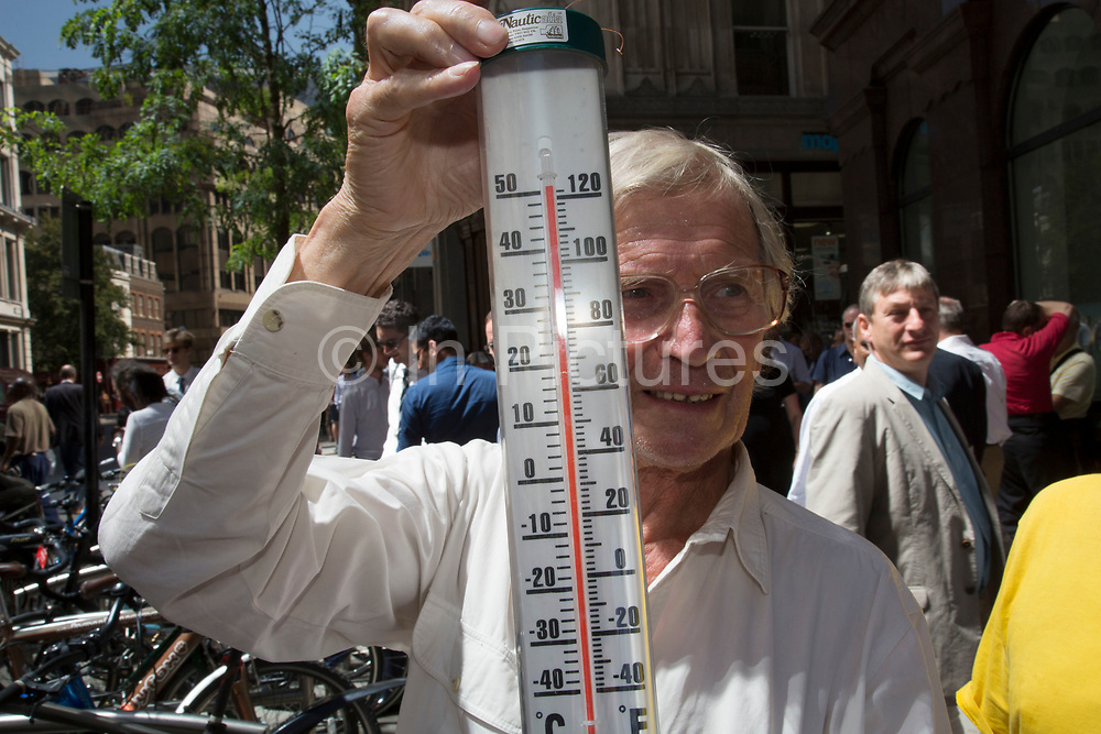 """London, UK. Thursday 5th September 2013. Man with a thermometer shows the temperature exceeding 50 degrees C, beyond the limit of his guage. Urgent action in planned to """"cover up"""" the Walkie Talkie skyscraper in the City after sunlight reflected from the building melted a car on the streets below. Temperatures have been measured in excess of 50 degrees C, and as much as 70 degrees at it's peak. The 525ft building has been renamed the """"Walkie Scorchie"""" after its distinctive concave surfaces reflected a dazzling beam of light which has caused extensive damage to nearby buildings."""