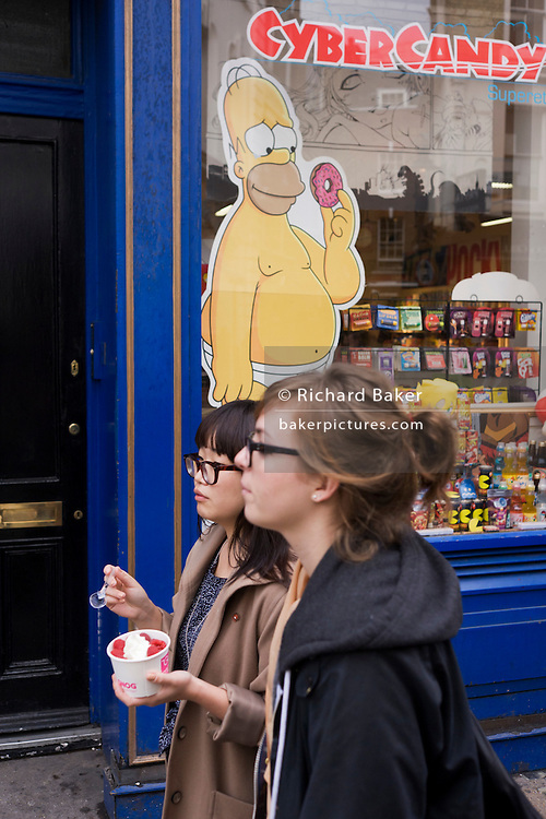 Homer Simpson cartoon character and women passers-by holding ice cream in central London.