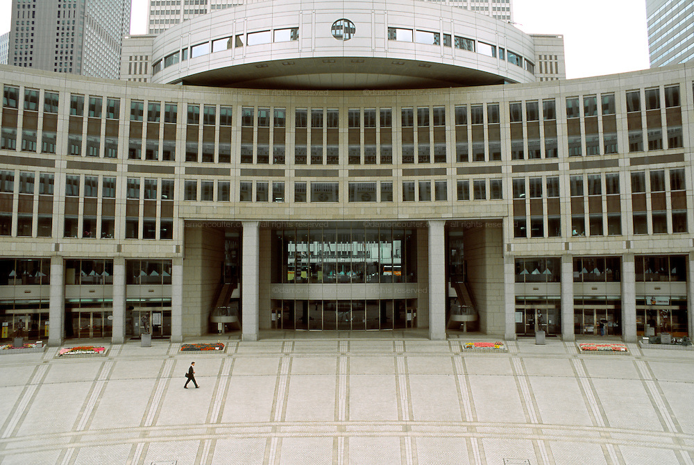 A businessmen walks across a plaza under part of Tokyo Assembly building complex (TMG) in Shinjuku, Tokyo, Japan March 1st 2007