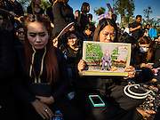 15 OCTOBER 2016 - BANGKOK, THAILAND: Women mourning the death of Bhumibol Adulyadej, the King of Thailand, sit on the sidewalk in front of the Grand Palace in Bangkok. King Bhumibol Adulyadej died Oct. 13, 2016. He was 88. His death comes after a period of failing health. With the king's death, the world's longest-reigning monarch is Queen Elizabeth II, who ascended to the British throne in 1952. Bhumibol Adulyadej, was born in Cambridge, MA, on 5 December 1927. He was the ninth monarch of Thailand from the Chakri Dynasty and is known as Rama IX. He became King on June 9, 1946 and served as King of Thailand for 70 years, 126 days. He was, at the time of his death, the world's longest-serving head of state and the longest-reigning monarch in Thai history.      PHOTO BY JACK KURTZ