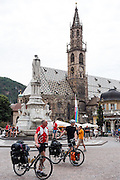 Bicycle campers walk by the medieval church in the main square of Bolzano, Walther Square, in the Dolomites, Trentino-Alto Adige/Südtirol (South Tyrol) region of Italy, Europe. Bolzano's Assumption of Our Lady Cathedral was started in 1184 in Romanesque style and expanded by 1382 using Gothic architecture. The steeple was completed in 1517. An 1889 monument in the center of Walther Square honors Walther von der Vogelweide, a great poet and bard who lived circa 1168-1228. Bolzano is the biggest city in South Tyrol, which is an autonomous province with a special statute which preserves the rights of the German-speaking minority in Italy. Bolzano has been voted as one of the most liveable of 100+ Italian cities. I'm not surprised, as several pedestrian-only streets downtown had a wonderfully vibrant ambiance (once you park and get out of the stressful spaghetti of auto traffic).