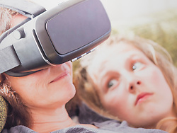 Girl looking at mother using virtual reality headset while relaxing on sofa