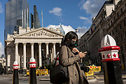On the day that Chancellor of the Exchequer Rishi Sunak unveiled a £30bn package to boost the economy and get the country through the coronavirus outbreak, an Asian lady wearing a surgical mask walks past Royal Exchange in the capital's financial district, as the Bank of England's governor Mark Carney cut the interest rate from 0.75% to 0.25%, on 11th March 2020, in the City of London, England.