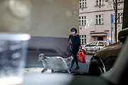Face masks are mandatory in public life in the Czech Republic. Woman walking her dog with a face mask in Prague Zizkov.