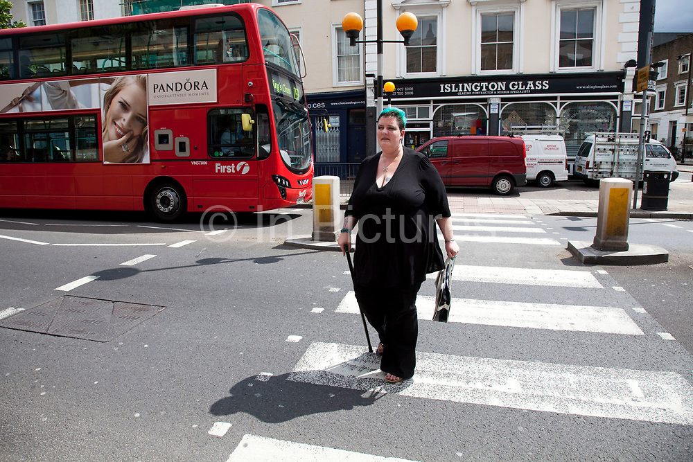 Mother Louise Irwin-Ryan walking to the shops in her neighbourhood of Barnsbury, near to Kings Cross, North London. Louise is on various benefits to help support her family income, and housing, although recent government changes to benefits may affect her family drastically, possibly meaning they may have to move out of London. Louise Ryan was born on the Wirral peninsula in 1970.  She moved to London with her family in 1980.  Having lived in both Manchester and Ireland, she now lives permanently in North London with her husband and two children. Through the years Louise has battled to recover from a serious motorcycle accident in 1992 and has recently been diagnosed with Bipolar Affective Disorder. (Photo by Mike Kemp/For The Washington Post)