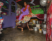 Meera, a young woman living in the slum, cleans the floor of the family home whilst her mother sits on the bed, Tangra slum, Dhipi, Kolkata, India