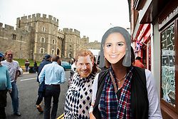 © Licensed to London News Pictures. 16/05/2018. Windsor, UK. People wear Prince Harry and Meghan Markle masks outside Windsor Castle. Prince Harry and Meghan Markle are to be married on Saturday in Windsor. Photo credit: Rob Pinney/LNP