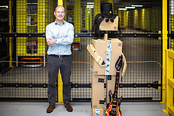 "© Licensed to London News Pictures . 04/12/2019. Manchester , UK .  General Manager of MAN1 warehouse NEIL TRAVIS poses beside a parcel puppet of Guns N' Roses guitarist Slash  . Inside the ""MAN1"" Amazon fulfilment centre warehouse at Manchester Airport in the North West of England . Photo credit : Joel Goodman/LNP"