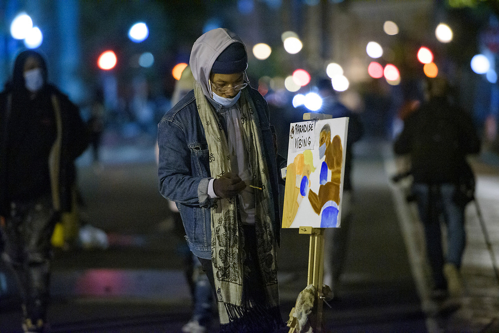 A protester paints while media and other protestors wait for the results of the presidential election at Black Lives Matter Plaza in Washington DC, November 3, 2020.