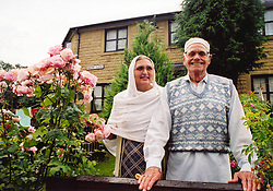 Asian couple in front of their house; Halifax; West Yorkshire,
