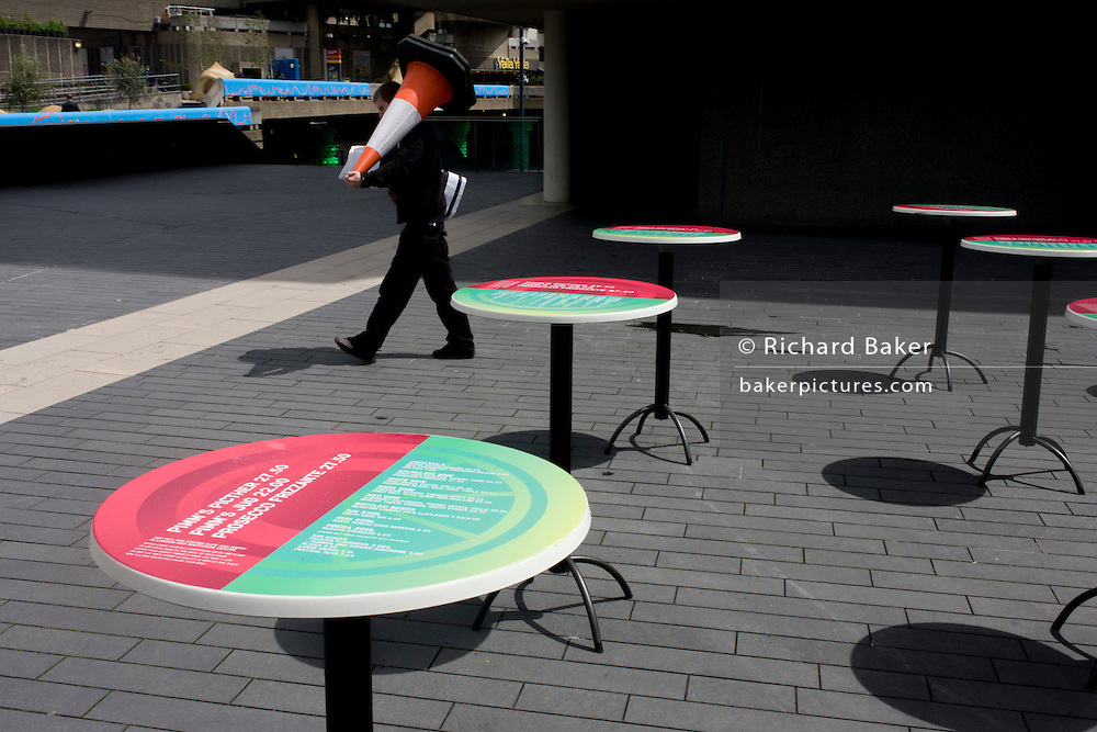Man carrying large traffic cone past vacant cafe tables in pedestrian pavement at London's Southbank.