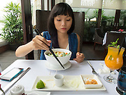 A young Vietnamese lady enjoying a lunch of pho (Vietnamese noodles) in a luxurious river side restaurant.