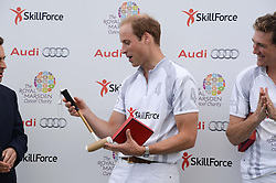 HRH THE DUKE OF CAMBRIDGE holding a gift of a miniture polo stick for HRH Prince George of Cambridge at the Audi Polo Challenge 2013 at Coworth Park Polo Club, Berkshire on 3rd August 2013.
