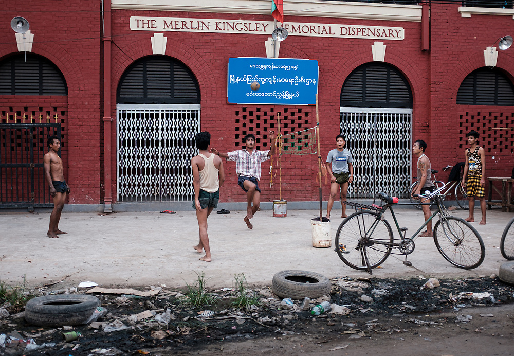 YANGON, MYANMAR - CIRCA DECEMBER 2017:  Men in the streets of Yangon playing Chinlone, also known as Caneball. This is a traditional, national sport of Myanmar (Burma). It is non-competitive, with typically six people playing together as one team.