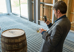 'Rebus' creator Ian Rankin can't resist taking photo mementos of one of the barrels after the author opened Scotland's newest distillery at Lindores Abbey in Fife, which is on the site of the earliest recorded distillation of whisky over 500 years ago.<br /> <br /> © Dave Johnston/ EEm