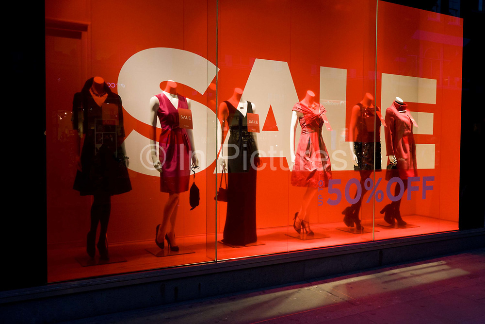 Sale sign and mannequins in a window of clothing emporium Hobbs in London's Long Acre. Giant letters lure potential customers into this branch of Hobbs with a Sale offer sign. Their mannequins are seen in the window of London's Long Acre (street) clothing shop - a line-up of womens' fashion variations displayed in the window on a winter's afternoon. Further reductions are also promised if the potential customer enters the store. With an economic recession taking hold on Britain's high streets and exclusive retail outlets, deals and offers are vital to keep spending and turnover up.