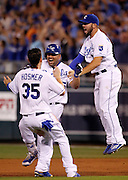 Kansas City Royals designated hitter Kendrys Morales, center, celebrates his game-winning hit with Eric Hosmer, left, and Mike Moustakas, right, in the 10th inning of a baseball game against the Los Angeles Angels at Kauffman Stadium in Kansas City, Mo., Sunday, Aug. 16, 2015. (AP Photo/Colin E. Braley)