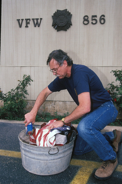 Anglo male veteran shows proper way to dispose of old flags at VFW (Veterans of Foreign Wars) hall in Austin, Texas.<br /> ©Bob Daemmrich/