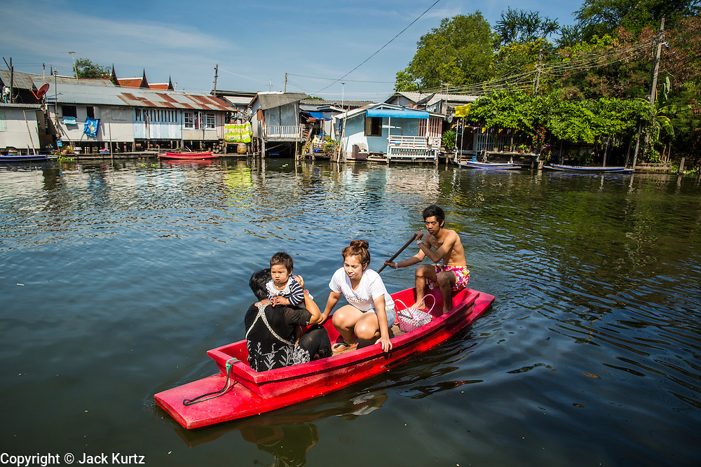 03 JANUARY 2013 - BANGKOK, THAILAND:  A family rows their canoe across Phra Khanong canal near Wat Mahabut. Just a few minutes from downtown Bangkok, the neighborhoods around Wat Mahabut interlaced with canals, still resemble the Bangkok of 60 years ago. Wat Mahabut is a large temple off Sukhumvit Soi 77. The temple is the site of many shrines to Thai ghosts. Many fortune tellers also work on the temple's grounds.   PHOTO BY JACK KURTZ