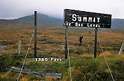 A lone walker passes by a partially-collapsed broken sign announcing the summit of Rannoch Moor, Scotland UK, 1,350 feet above sea level. He is hunched against a driving wind at this altitude and the country he is walking over is bleak and boggy, a wetland high up in the Scottish Highlands. Thick tufts of grass and moss lie about in this tough terrain, held in great affection for long-distance hikers. Rannoch Moor is a large expanse of around 50 square miles (130 km²) of boggy moorland to the west of Loch Rannoch, in Perth and Kinross and Lochaber, Highland, partly northern Argyll and Bute, Scotland. Rannoch Moor is designated a National Heritage site.