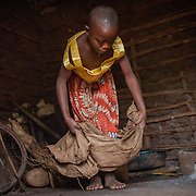 CAPTION: Juliet, who lives with a hearing impairment, cleans up her family home before preparing for school in the morning. Economic factors that force children like Juliet and their families to sleep on the floor and function without running water can exacerbate hearing impairment thanks to the poor personal hygiene that's hard to avoid under these circumstances. SignHealth Uganda has helped Juliet by providing her with medical treatment to improve her hearing. LOCATION: Butenga Village, near Masaka City, Bukomansimbi District, Central Region, Uganda. INDIVIDUAL(S) PHOTOGRAPHED: Juliet Nassuna.