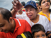 31 AUGUST 2014 - SARIKA, NAKHON NAYOK, THAILAND: People crowd around to try to touch the Ganesh statue as it is taken to a nearby river to be submerged during the Ganesh Festival Shri Utthayan Ganesha Temple in Sarika, Nakhon Nayok. Ganesh Chaturthi, also known as Vinayaka Chaturthi, is a Hindu festival dedicated to Lord Ganesh. It is a 10-day festival marking the birthday of Ganesh, who is widely worshiped for his auspicious beginnings. Ganesh is the patron of arts and sciences, the deity of intellect and wisdom -- identified by his elephant head. The holiday is celebrated for 10 days, in 2014, most Hindu temples will submerge their Ganesh shrines and deities on September 7. Wat Utthaya Ganesh in Nakhon Nayok province, is a Buddhist temple that venerates Ganesh, who is popular with Thai Buddhists. The temple draws both Buddhists and Hindus and celebrates the Ganesh holiday a week ahead of most other places.    PHOTO BY JACK KURTZ