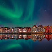One of the most beautiful nights in Trondheim. I was trying to capture the northern light above the Nidelva and bakklandet. You see the colorful wooden houses and the greenish sky . IT was such a wonderful