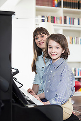 Mother and daughter playing piano, smiling