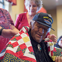 Navajo code talker Roy Hathorne is wrapped in a hand made quilt of valor by volunteers Shelly Young, left, and Marjorie Polich Thursday in Gallup.