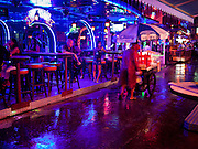 "12 JULY 2011 - BANGKOK, THAILAND: A noodle vendor pushes his cart past a beer bar frequented by prostitutes and their customers on Soi Cowboy, a ""red light"" district in Bangkok during a rainy season downpour.  Prostitution in Thailand is illegal, although in practice it is tolerated and partly regulated. Prostitution is practiced openly throughout the country. The number of prostitutes is difficult to determine, estimates vary widely. Since the Vietnam War, Thailand has gained international notoriety among travelers from many countries as a sex tourism destination. One estimate published in 2003 placed the trade at US$ 4.3 billion per year or about three percent of the Thai economy. It has been suggested that at least 10% of tourist dollars may be spent on the sex trade. According to a 2001 report by the World Health Organisation: ""There are between 150,000 and 200,000 sex workers (in Thailand).""  PHOTO BY JACK KURTZ"
