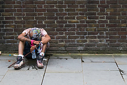 London, August 30th 2015. A drunk reveller throws up on a side street as tens of thousands enjoy the food and alcohol available in the Notting Hill Carnival.