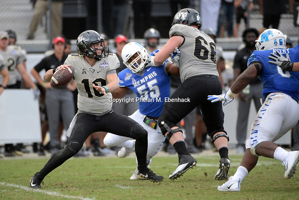 Central Florida quarterback McKenzie Milton (10) sets up to throw a pass in front of Memphis linebacker Genard Avery (6) and linebacker Bryce Huff (55) during the second half of the American Athletic Conference championship NCAA college football game Saturday, Dec. 2, 2017, in Orlando, Fla. Central Florida won 62-55. (Photo by Phelan M. Ebenhack)
