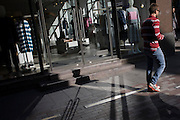Afternoon relflected light on pavement and in shop window selling womens' wear