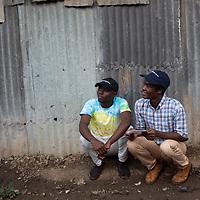Bahati Kituli and Philip Ocheche, mentors on sexual health and reproductive rights, confer before giving a talk to a group in Mukuru Kwa Njenga, Nairobi.