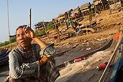 FISHERMEN MEKONG RIVER. South East Asia, Cambodia, Phnom Penh, Mekong River. The Cham fisher people live in various desolated villages along the banks of the Mekong and Tonle Sap rivers. The fisher families live like river gypsy nomads, working and living on their boats, sleeping under a sprung bamboo frame, all their worldly goods stored below deck. They live in extended families, with numerous boats, together for safety. Their diet is rice, vegetables and fish. Their sleek wooden boats are powered by petrol outboard motors with batteries or generators to supply lighting at night. Their fishing technique is laying nets twice or three times per day, which are weighted well below the surface, using old paint aerosal canisters as buoyant floaters, hanging just beneath the surface. These particular fisher families, living at the junction of the Mekong and Tonle Sap rivers, overlooked by Phnom Penh, sell their catch at the Vietnamese market, on the banks of the river. Their life and fortunes are controlled by the cycle of the river. As the river levels drop, so the quantity of fish decreases, until after the heavy floods of the monsoon they fill the river again. They are poor traditional Muslims, marginalised from mainstream society, living a third world life in the immmediate shadow of the first world. The Cham, originally a people of an ancient kingdom called Champa, are a small and disenfranchised community who were disinherited of their land. They are a socially important ethnic group in Cambodia, numbering close to 300,000. The Cham people, live in some 400 villages across Kampong Chnang and Kampong Cham provinces. Their religion is Muslim and their language belongs to the Malayo-Polynesian family. Their livelihoods are as diverse as rice farming, cattle trading, hunting and fishing.///A Cham fisherman smokes a cigarette, behind him typical flimsy squats and temporary houses built on the river banks on stilts