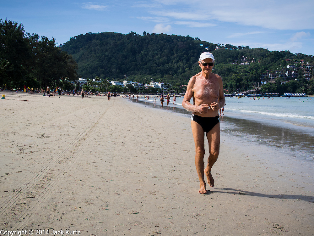 27 DECEMBER 2014 - PATONG, PHUKET, THAILAND: A man jogs on Patong Beach. Patong Beach is the largest beach on Phuket island. It's popular with tourists from Australia and Europe. In recent years it has become a leading destination for Russian tourists.    PHOTO BY JACK KURTZ