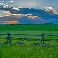 The sun sets behind a thunderstorm rain squall in the Gallatin Valley, near Bozeman, Montana. In the foreground are hay fields and a jack leg fence.