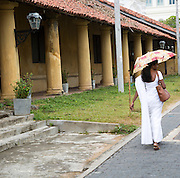 Woman walking with umbrella for shade in the historic town of Galle, Sri Lanka, Asia