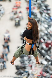 Paschelle Carter of Sacramento, CA rides the zip line over Main Street during the annual Sturgis Black Hills Motorcycle Rally. Sturgis, SD, USA. August 6, 2014.  Photography ©2014 Michael Lichter.