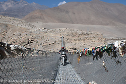Michael Lichter riding across a narrow suspension bridge over the Kali Gandaki River on day-6 of our Himalayan Heroes adventure riding from Muktinath to Tatopani, Nepal. Sunday, November 11, 2018. Photography ©2018 Michael Lichter.