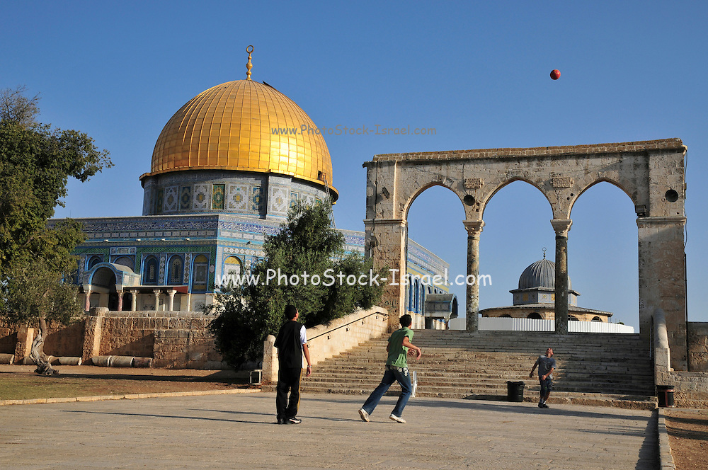 Israel, Jerusalem Old City, Dome of the Rock on Haram esh Sharif (Temple Mount) a Qanatir (The Arch) in the foreground. Arab children play soccer