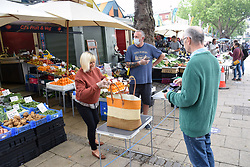 Social distancing measures in operation in Norwich market during Coronavirus lockdown, UK June 2020. Fruit & veg stall