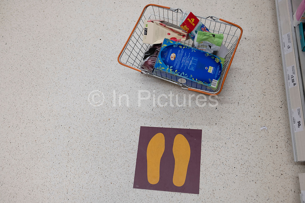 Shopping basket and social distancing markers in Sainsburys supermarket on 21st April 2020 in Birmingham, England, United Kingdom. Coronavirus or Covid-19 is a new respiratory illness that has not previously been seen in humans. While much or Europe has been placed into lockdown, the UK government has put in place more stringent rules as part of their long term strategy, and in particular social distancing.