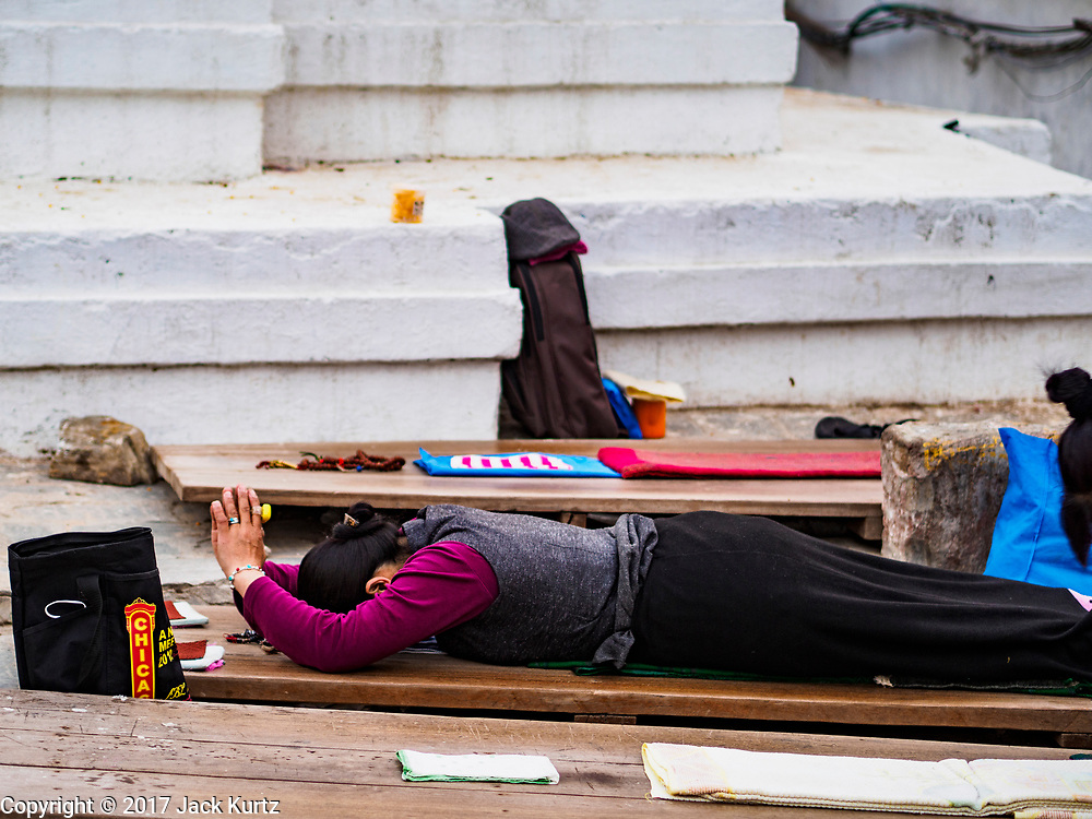17 MARCH 2017 - KATHMANDU, NEPAL: A woman prostrates herself during morning prayers at Boudhanath Stupa in Kathmandu. The stupa is the holiest site in Nepali Buddhism. It is also the center of the Tibetan exile community in Kathmandu. The Stupa was badly damaged in the 2015 earthquake but was one of the first buildings renovated.     PHOTO BY JACK KURTZ