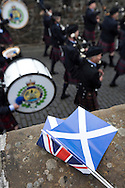 A Scottish saltire and a Union Jack lying on a wall as a traditional Scottish pipe band marches past during Pipefest Stirling, an event staged at Stirling Castle to coincide with the 700th anniversary of the Battle of Bannockburn. The event was attended by 1600 pipers, Highland dancers and other musicians and formed a procession through the city's streets. The Battle of Bannockburn took place in 1314 and resulted in the defeat of Edward II's English army by the Scots under Bruce.