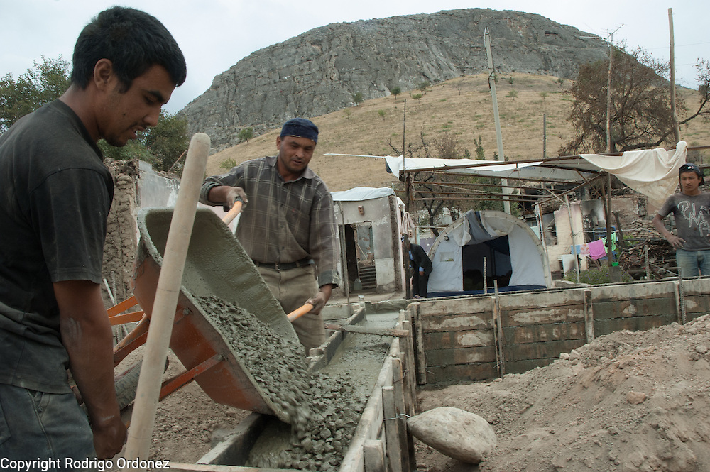 Construction workers pour concrete for the base foundation of a home supported by Save the Children in Kizil Kishtak (Osh, Kyrgyzstan) with Sulaiman Mountain on the background.