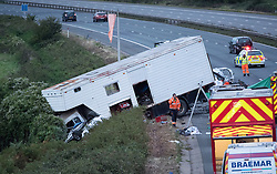 © Licensed to London News Pictures.  16/09/2017; Thornbury, South Gloucestershire, UK. Fatal accident on the M5 motorway. At least 4 people have died. A car can be seen upside down in front of the lorry cab. At just before 2.30pm, a lorry travelling southbound went through the central reservation and was in collision with at least two other vehicles in the northbound carriageway. Four people are believed to have died and a number of others have been taken to hospitals in the Bristol area. South Western Ambulance Service have been assisting casualties at the scene and sent 13 resources to the scene, including operations officers, two critical care paramedic teams, four hazardous area response teams (HART) and five double-crewed ambulances. Avon Fire & Rescue Service sent six appliances and its Major Rescue Tender to the scene. Picture credit : Simon Chapman/LNP