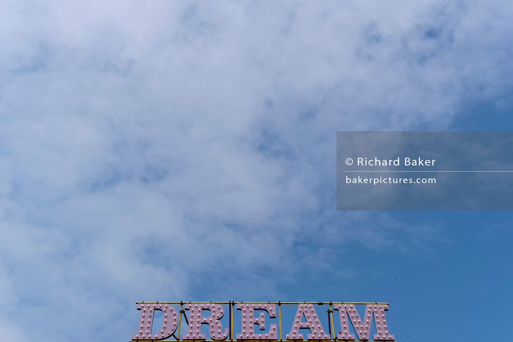 The word 'Dream' is beneath a blue sky and high cloud, at 'Dreamland', the historical funfair in the English seaside town of Margate, on 26th July, in Margate, Kent, England.