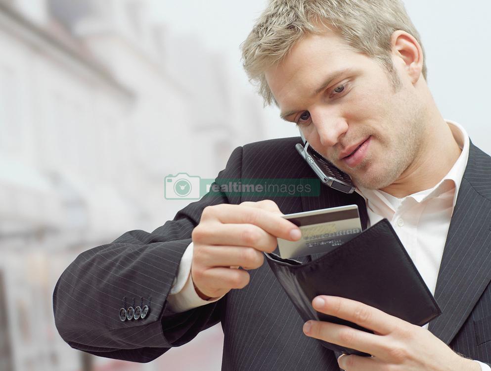 Dec. 14, 2012 - Man on mobile with credit card (Credit Image: © Image Source/ZUMAPRESS.com)